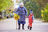 Senior woman and her great grandson in autumn park