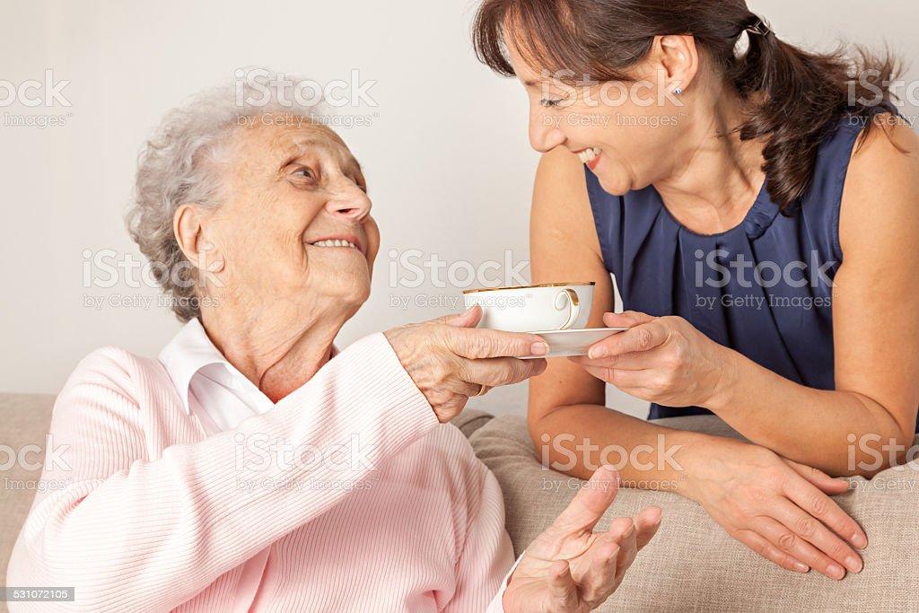 Senior woman and home caregiver having fun stock photo