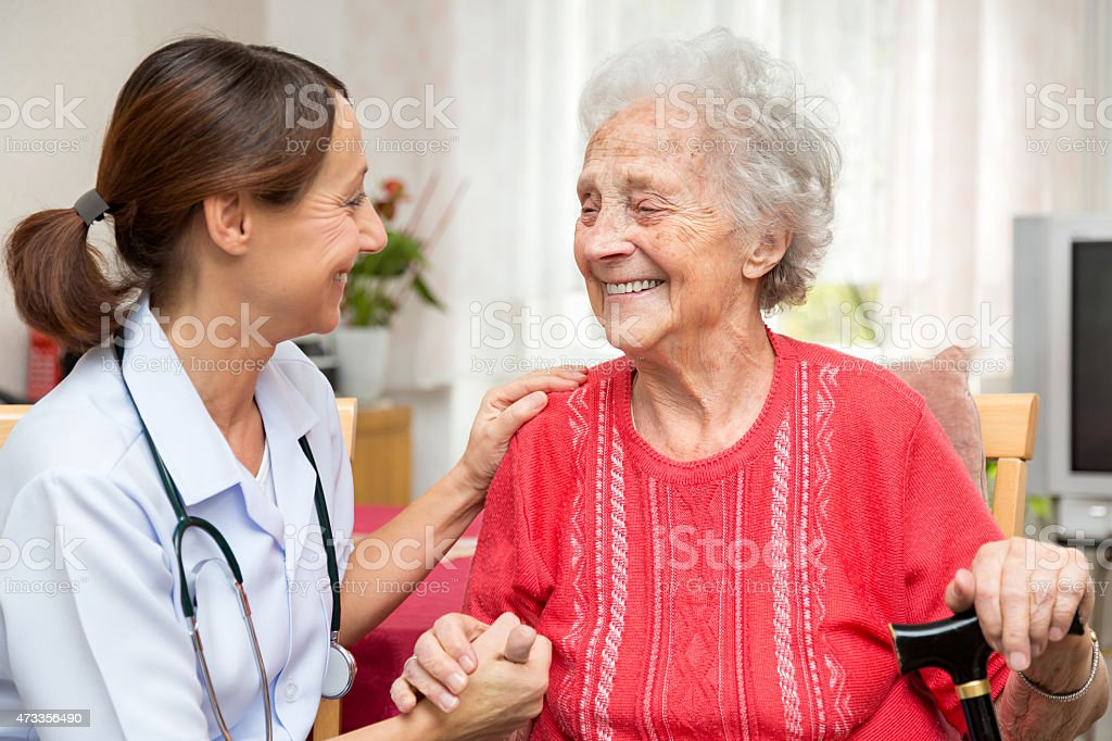 Senior woman and nurse holding hands stock photo