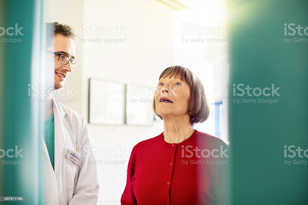 Senior woman and pharmacist standing in aisle at pharmacy stock photo