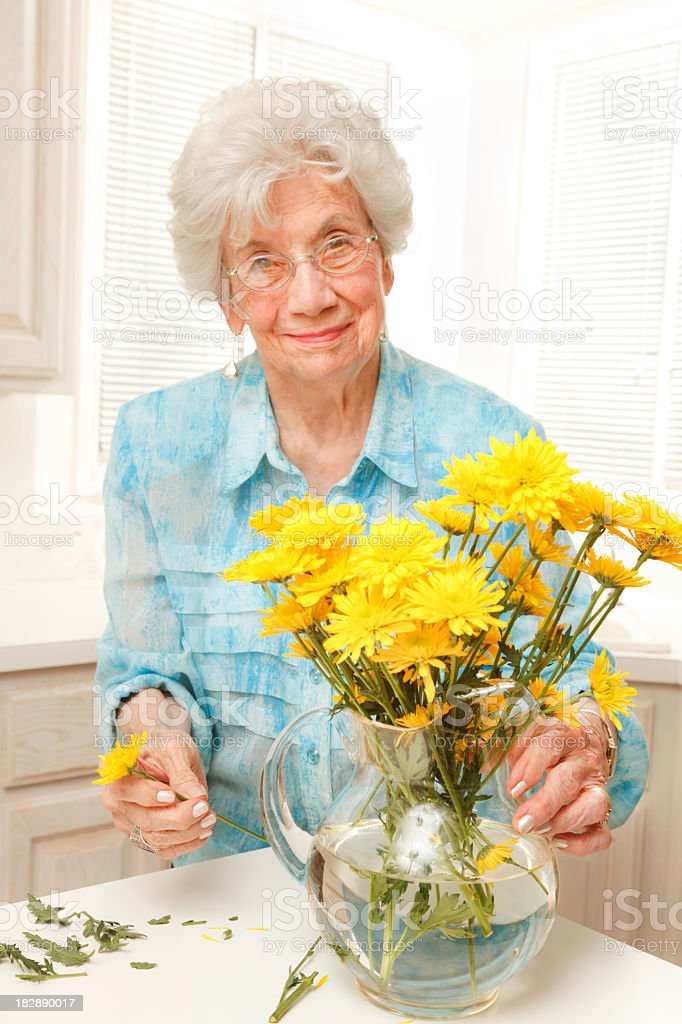 senior woman arranging cut yellow flowers in vase stock photo