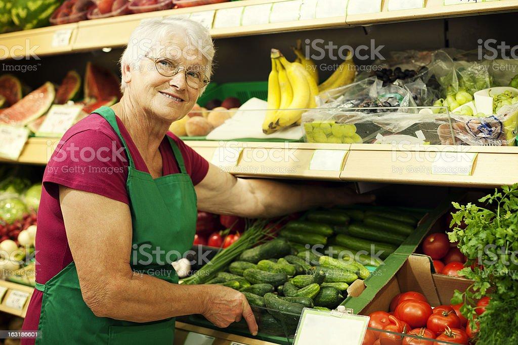 Senior woman arranging vegetables on shelf royalty-free stock photo