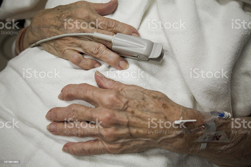 senior woman arthritis hands, oxygen sensor, IV drip, ER hospital stock photo