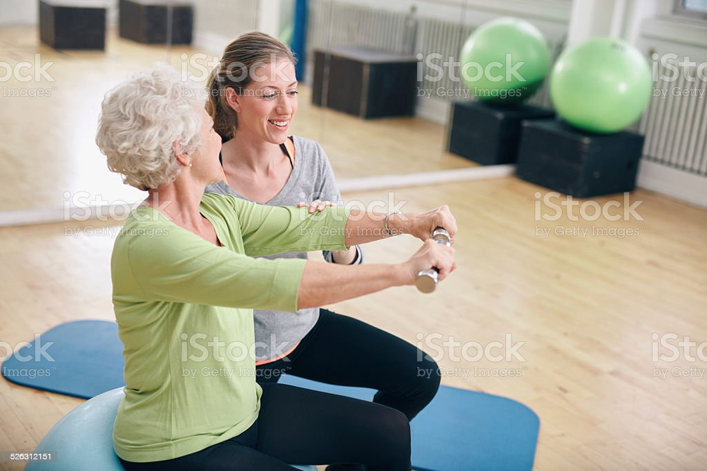Senior woman assisted by personal trainer in gym stock photo