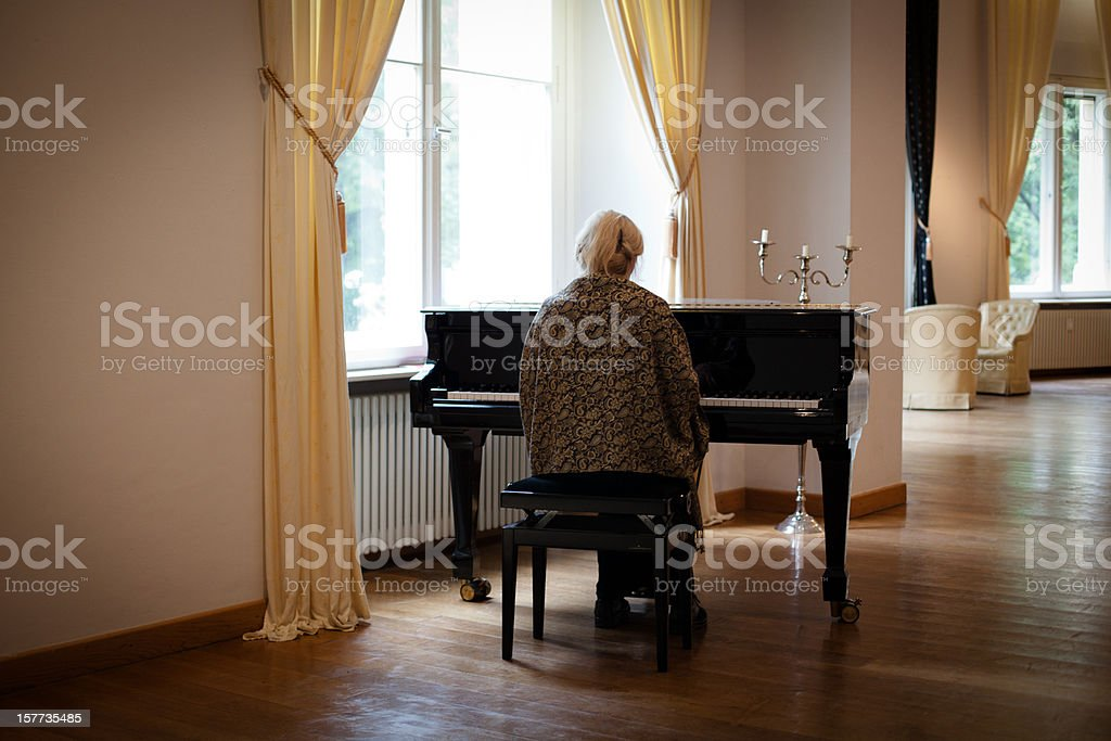 senior woman at a grand piano in an empty room stock photo