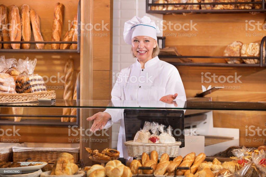 Senior woman at bakery display stock photo