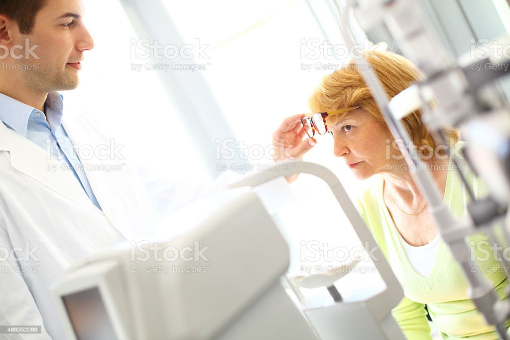 Senior woman at eye doctor. stock photo