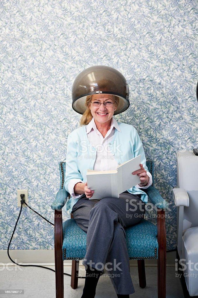 Senior woman at hair salon under dryer stock photo