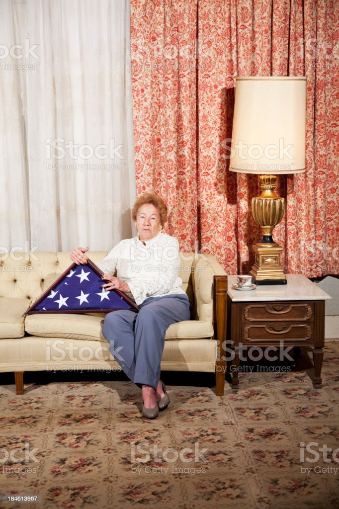 Senior woman at home holding folded American flag stock photo