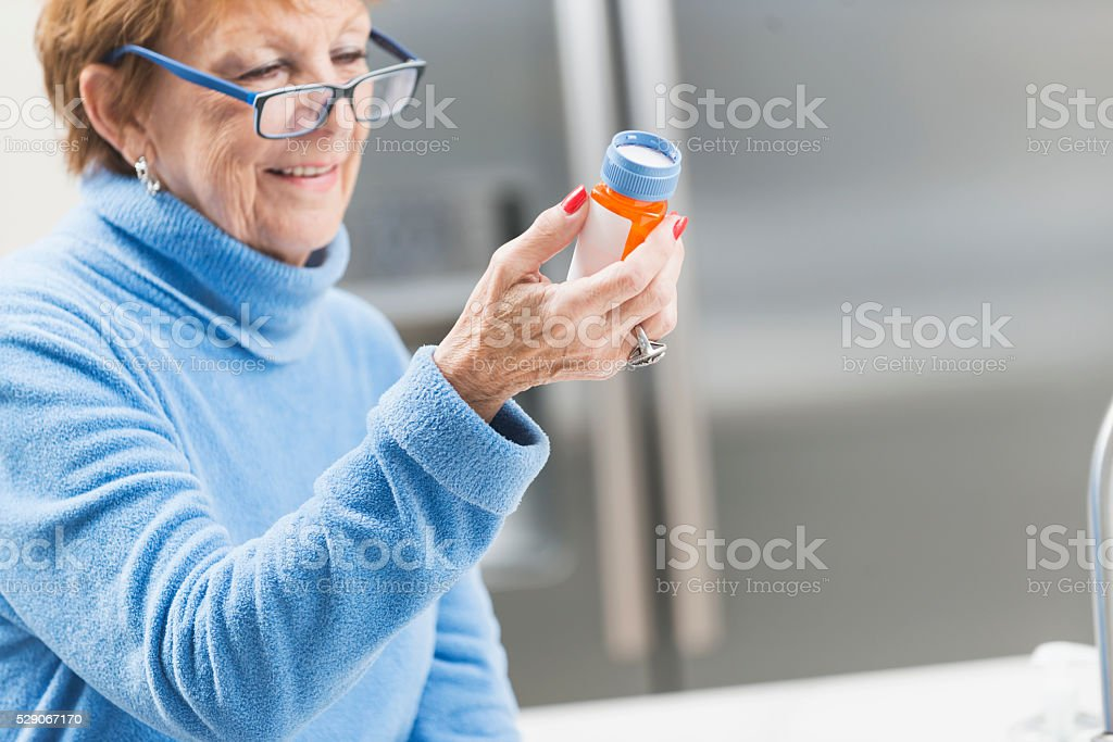 Senior woman at home reading label on prescription stock photo