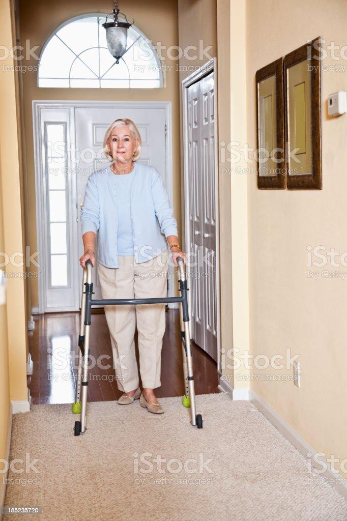 Senior woman at home using walker stock photo
