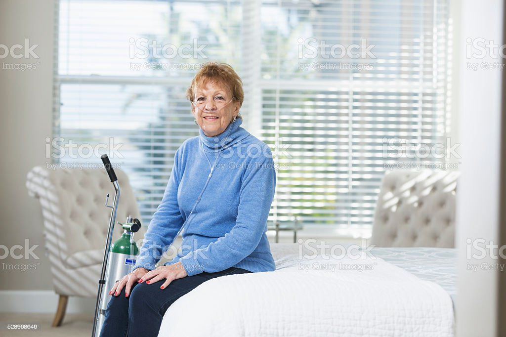 Senior woman at home with portable oxygen tank stock photo