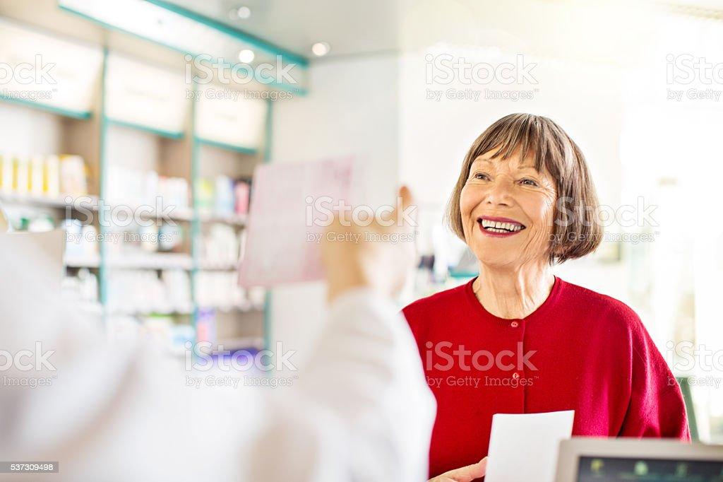 Senior woman at pharmacy drugstore checkout counter stock photo
