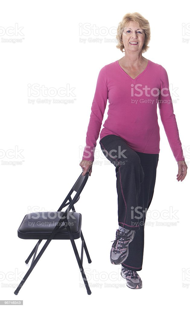 Senior woman balancing on one leg stock photo