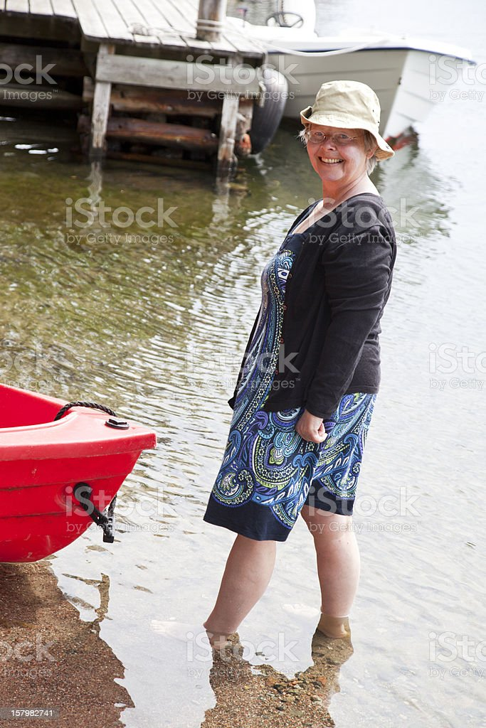 Senior woman barfoot in the sea with small red boat. stock photo