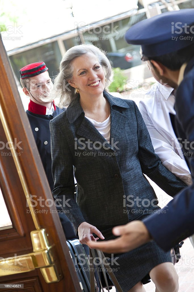 Senior woman being greeted at door by hotel doorman stock photo