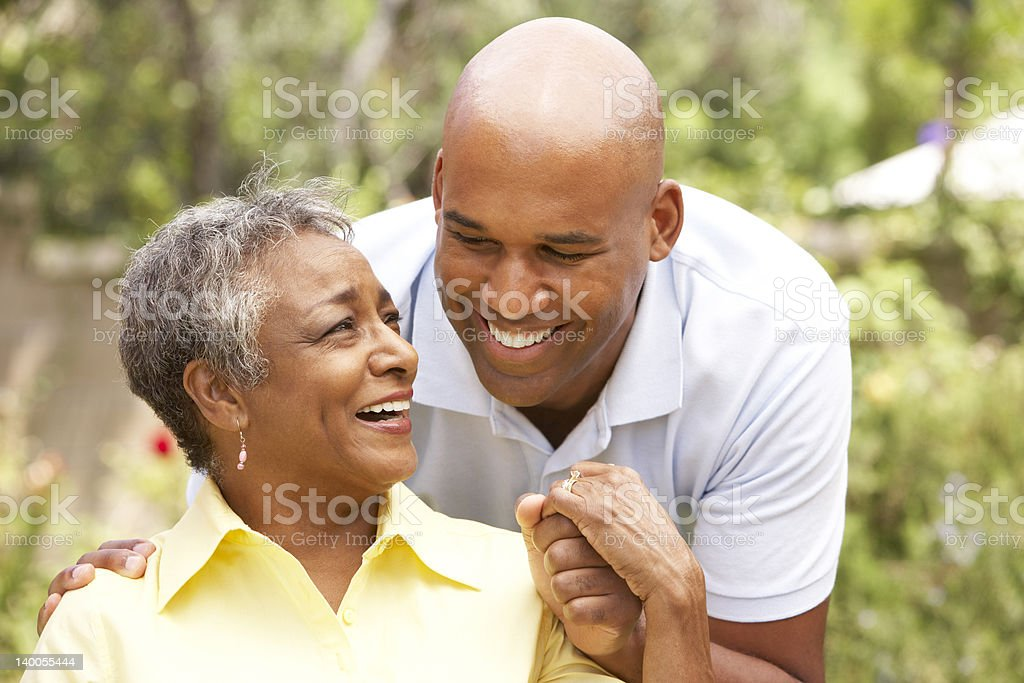 Senior Woman Being Hugged By Adult Son stock photo