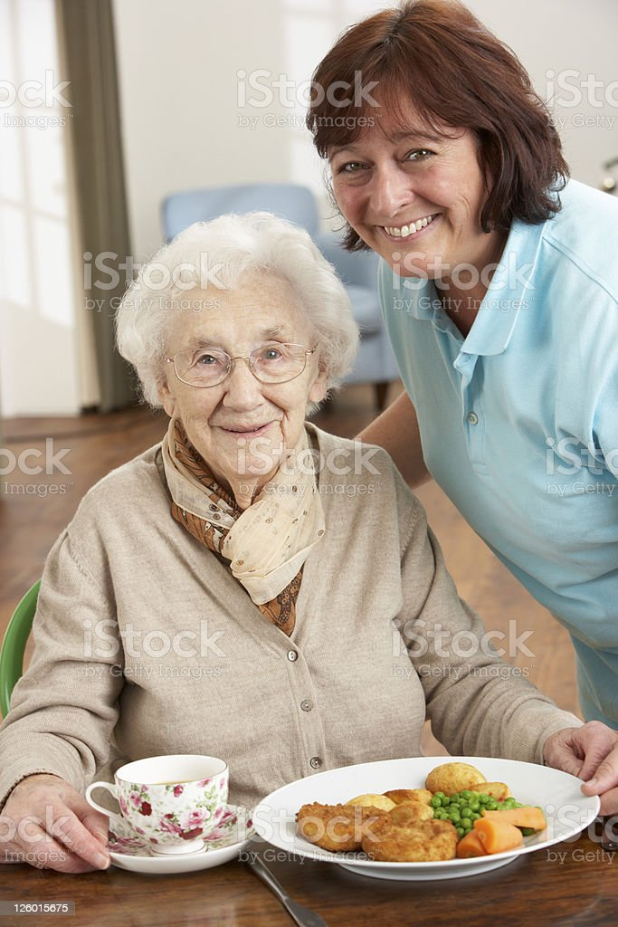 Senior Woman Being Served Meal By Carer royalty-free stock photo