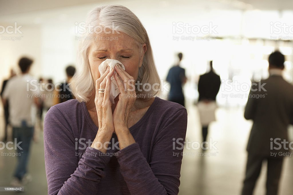 Senior woman blowing nose stock photo
