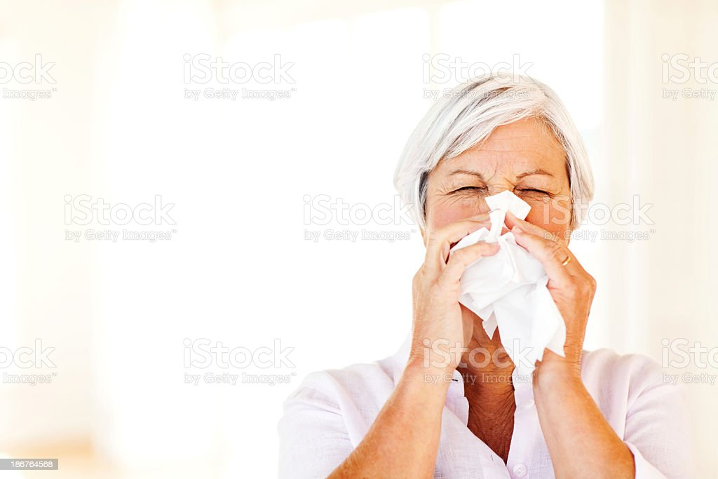 Senior Woman Blowing Nose With Tissue At Home royalty-free stock photo
