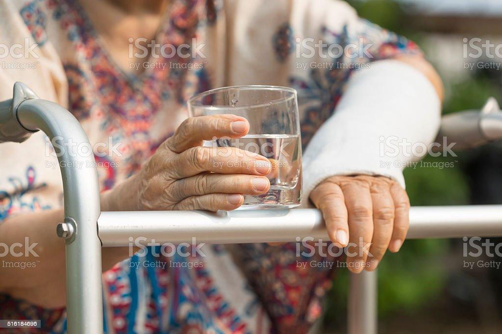 senior woman broken wrist using walker in backyard. stock photo