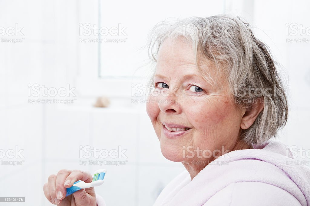 senior woman brushing teeth royalty-free stock photo