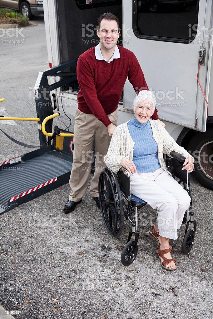 Senior woman by minibus with wheelchair lift stock photo