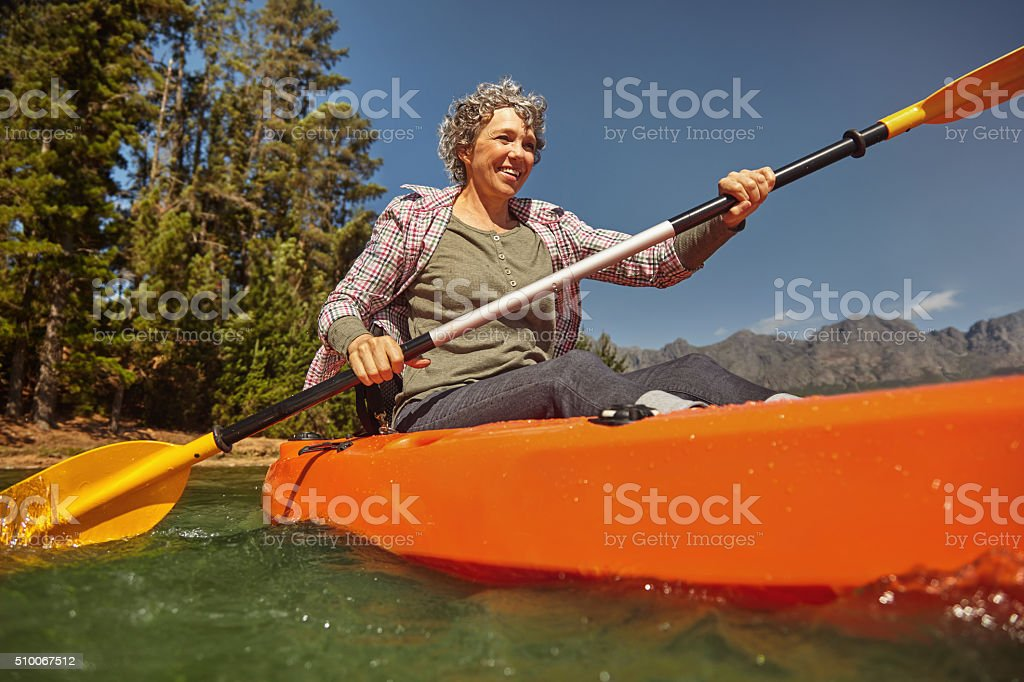 Senior woman canoeing on summer day stock photo