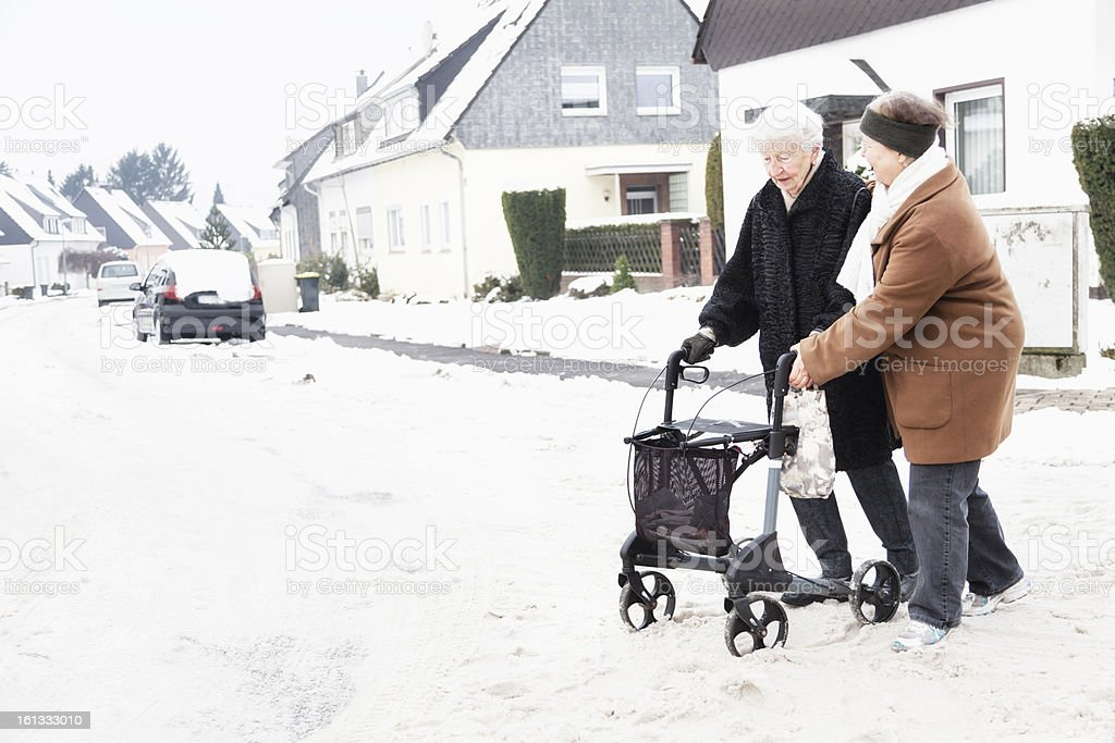 senior woman caregiver and walker on snow road stock photo