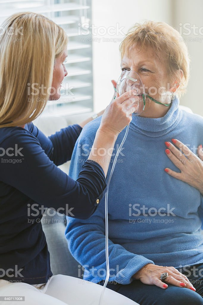 Senior woman, caregiver helping with oxygen mask stock photo