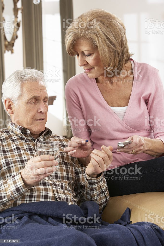 Senior Woman Caring For Sick Husband royalty-free stock photo