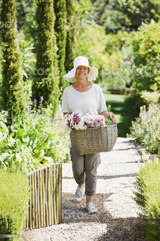 Senior woman carrying basket of flowers in garden royalty-free stock photo