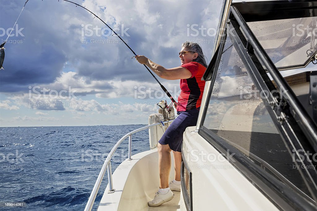 Senior Woman catching a fish royalty-free stock photo