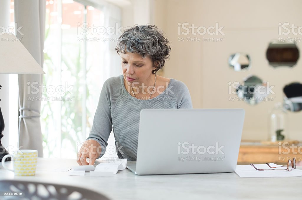 Senior woman checking bills stock photo
