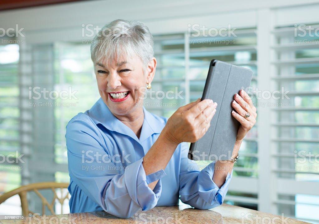 Senior woman checking digital tablet stock photo