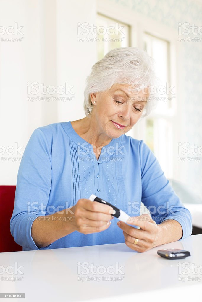 Senior Woman Checking Her Blood Sugar Level At Home stock photo