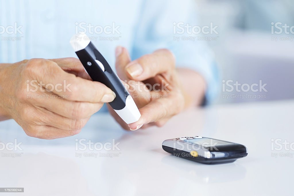 Senior Woman Checking Her Blood Sugar Level stock photo