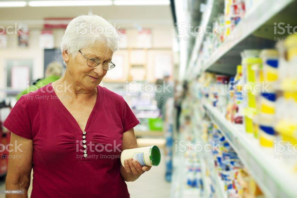Senior woman checking label on jar royalty-free stock photo