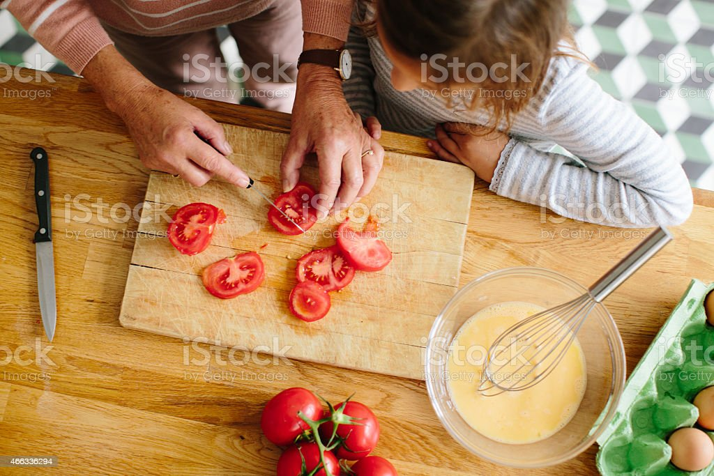Senior woman chopping tomatoes with her granddaughter in kitchen stock photo