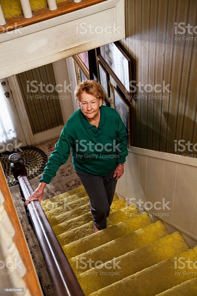 Senior woman climbing stairs stock photo