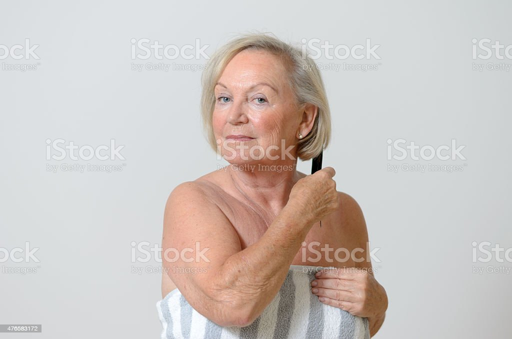 Senior woman combing her hair stock photo