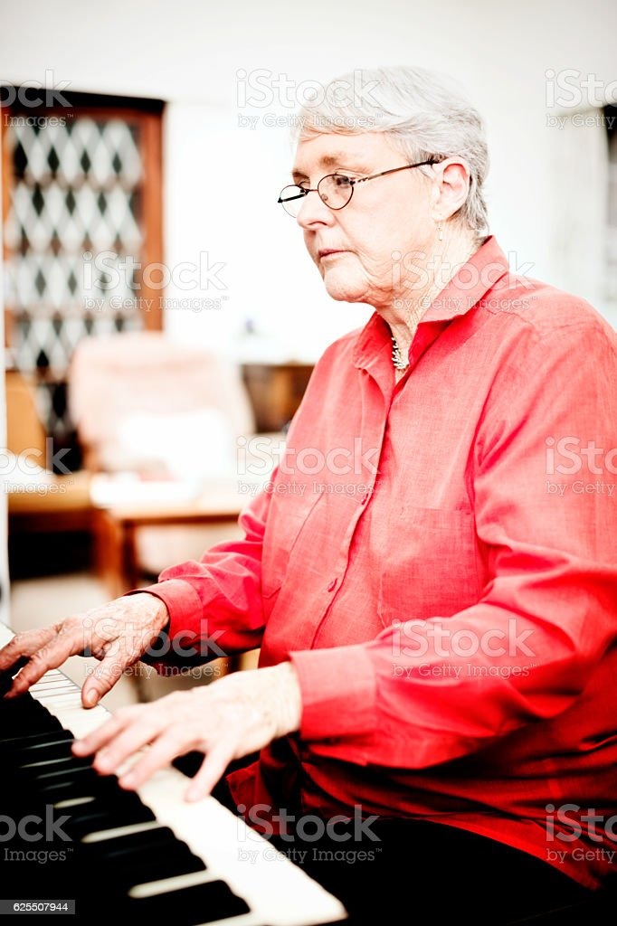 Senior woman concentrates as she plays the piano stock photo