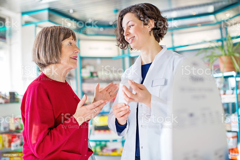 Senior woman consulting medicine dosage with the pharmacist stock photo