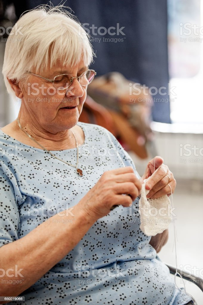 Senior Woman Crocheting At The Community Center stock photo