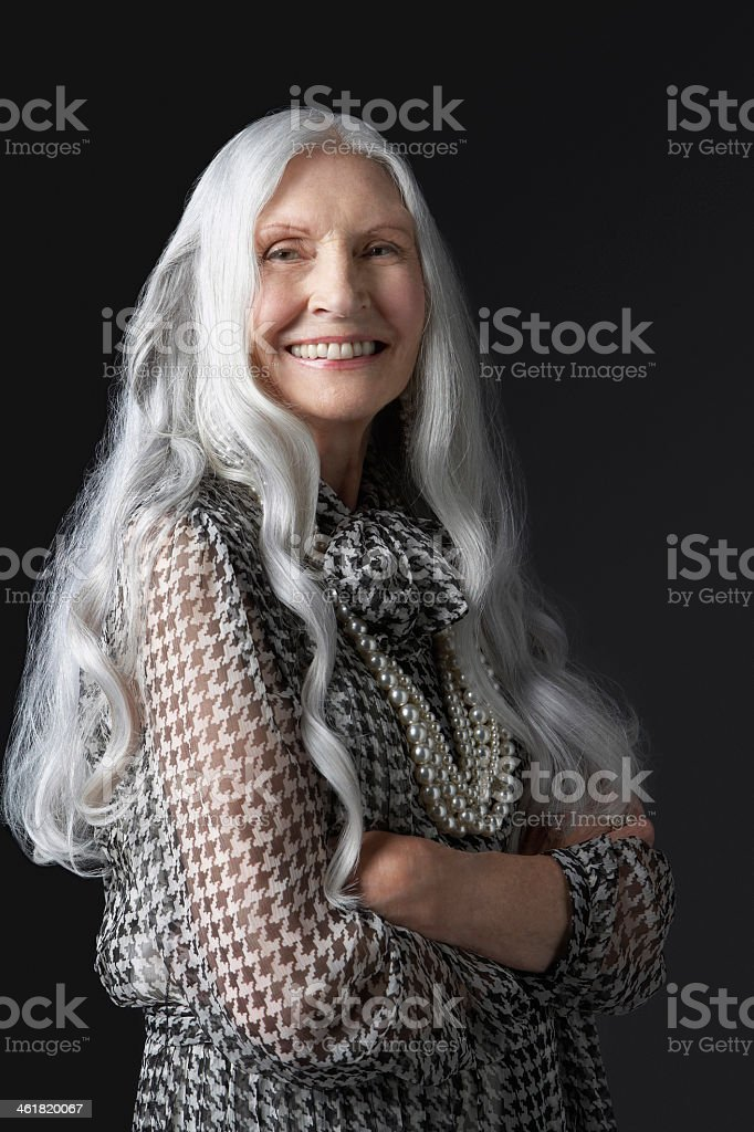 Senior woman crossing arms and smiling stock photo