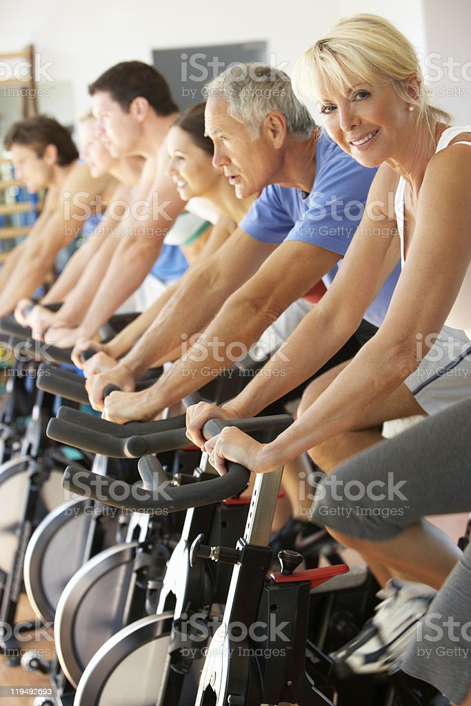 Senior Woman Cycling At Spinning Class In Gym stock photo
