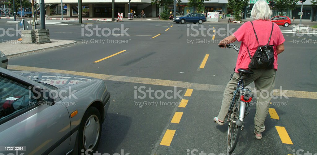 Senior woman cyclist waiting on crossing stock photo