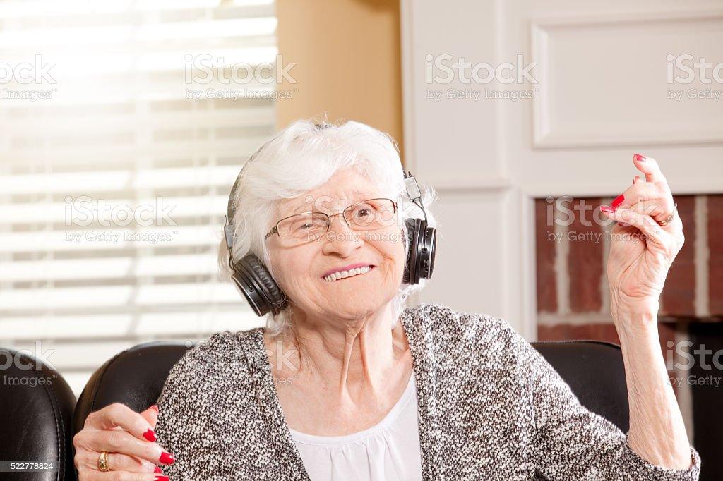 Senior Woman Dancing To Music On Headphones stock photo