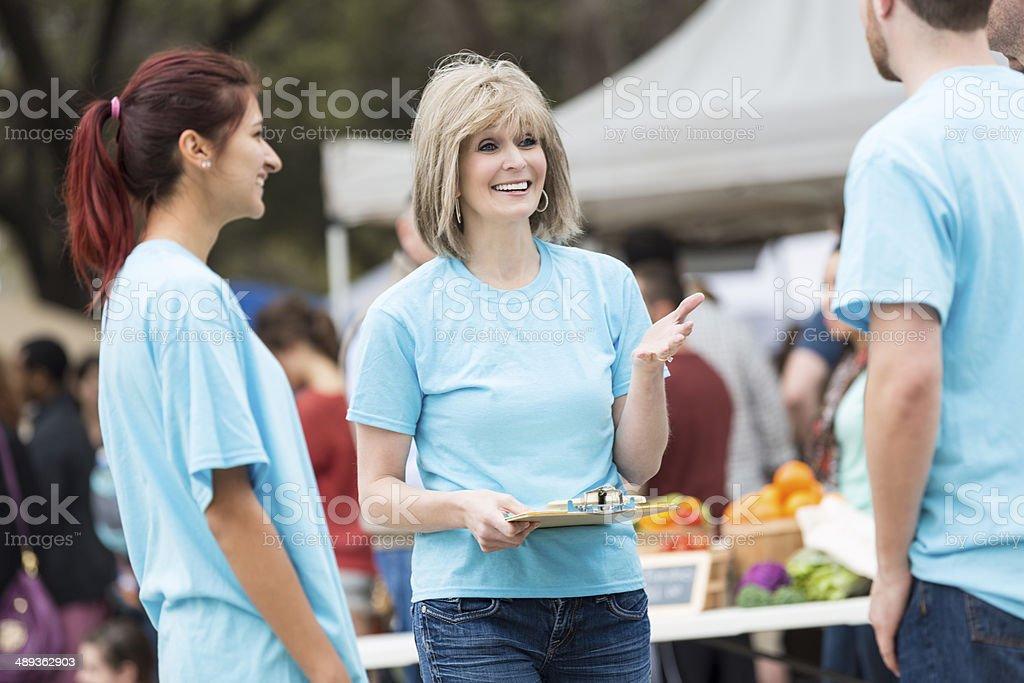 Senior woman directing volunteers at outdoor farmer's market stock photo