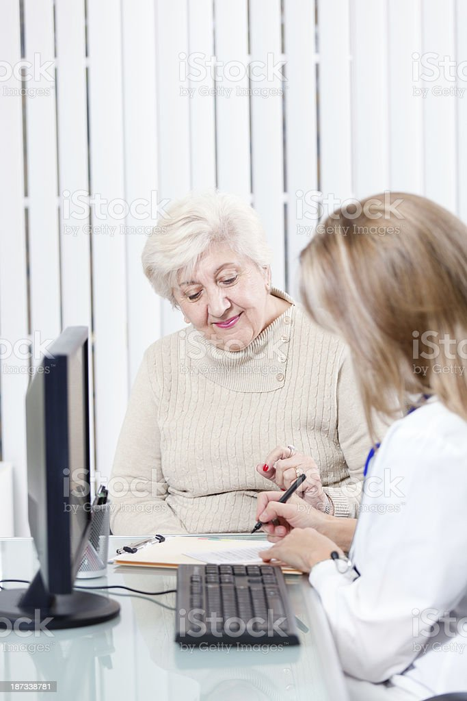 Senior Woman Discussing Healthcare Prescription with Physician at Clinic stock photo